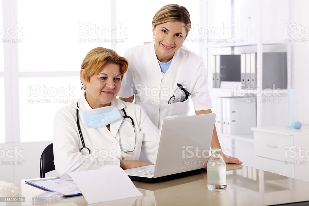 Two female doctors with laptop computer in the office royalty-free stock photo