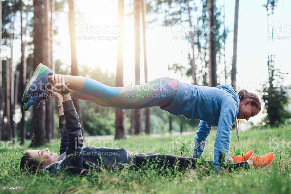 Two female friends doing partner plank exercise practicing pilates in the spring forest stock photo