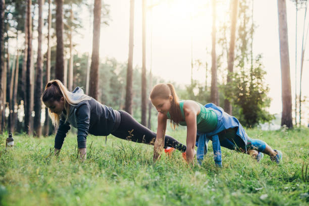 two female friends doing push-up exercise training outdoors in forest - peso mosca foto e immagini stock