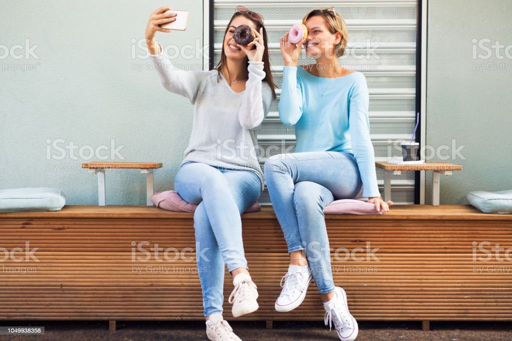Two female friends eating donuts and taking selfies stock photo