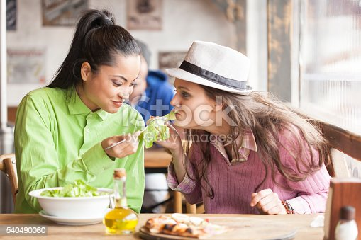 Two young women sitting in restaurant. One with ponytail eating fresh salad giving some at her friend with white hat. Slices of pizza, bowl of salad and coocking oil jug on table. Behind them young man dining. Focus on foreground. Windows and walls with pictures on background.