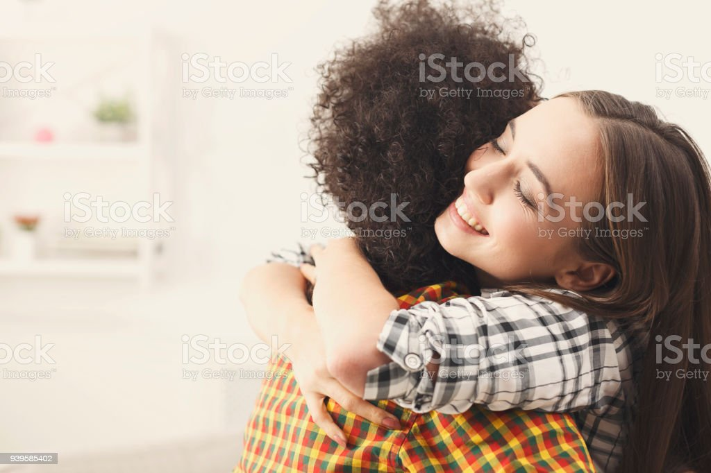 Two female friends embracing each other at home stock photo