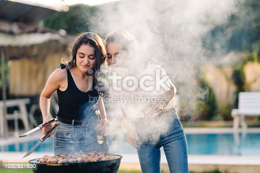 Two young female friends are enjoying bbq party.