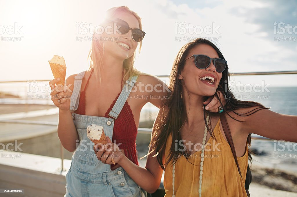 Two female friends enjoying ice cream together - Photo