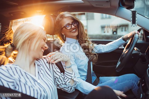 832085296 istock photo Two female friends enjoying road trip traveling at vacation in the car 1222417218