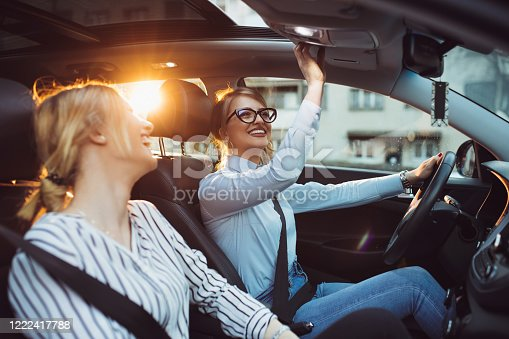832085296 istock photo Two female friends enjoying road trip traveling at vacation in the car 1222417788