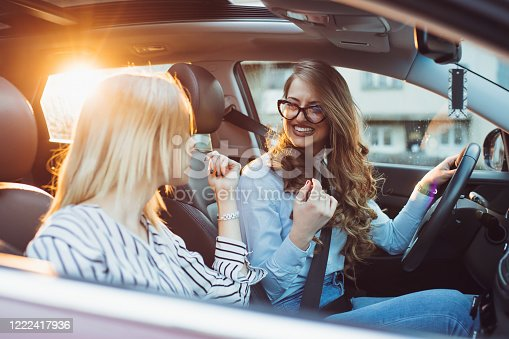 832085296 istock photo Two female friends enjoying road trip traveling at vacation in the car 1222417936