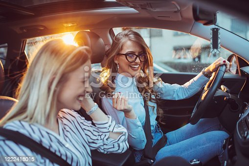 832085296 istock photo Two female friends enjoying road trip traveling at vacation in the car 1222418015