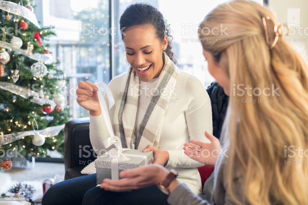 Two Female Friends Exchange Christmas Gifts On Couch Stock Photo ...