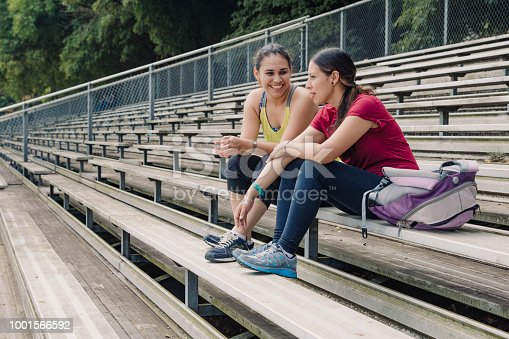 Two girl friends laughing at something while taking a break from exercising, sitting together, with their sports kit, there is a strong diagonal formed by the rows of seats, the area is fringed by trees, there is copy space to the left of the image.