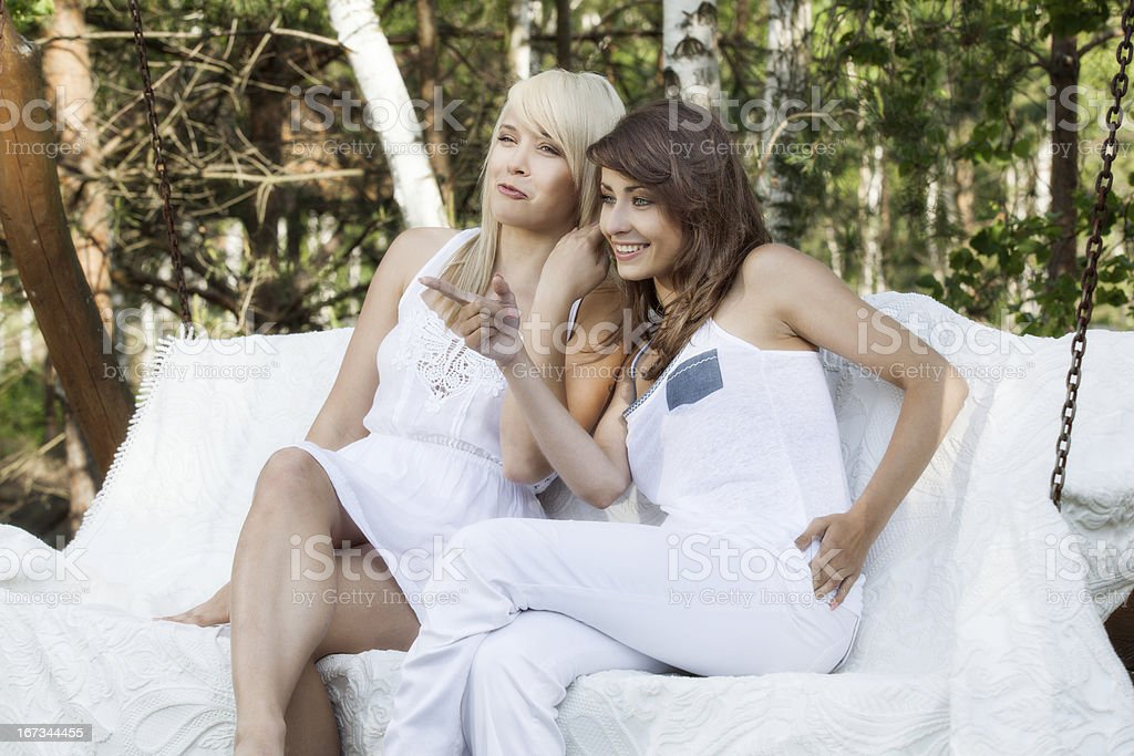 Two female friends gossiping stock photo