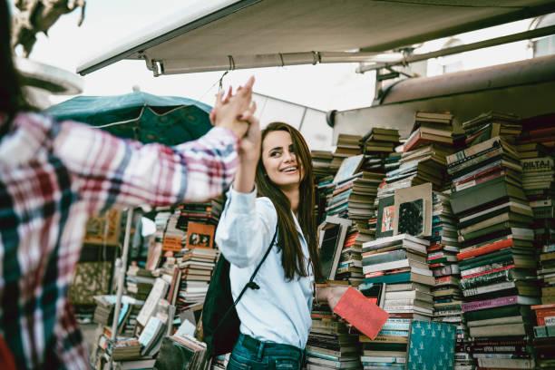 zwei freundinnen, die einander auf einen gruß buchmesse - gebrauchte bücher verkaufen stock-fotos und bilder