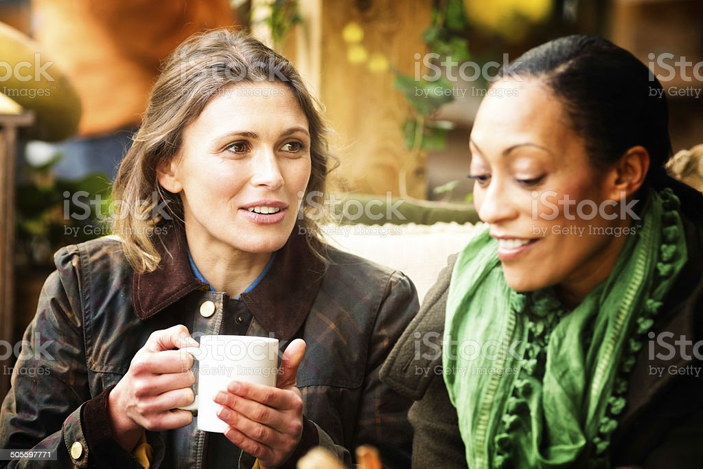 Two female friends having coffee at cafe stock photo