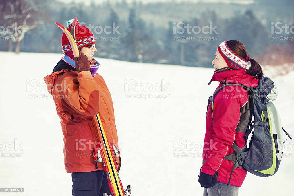 Two female friends hiking on snowy day royalty-free stock photo
