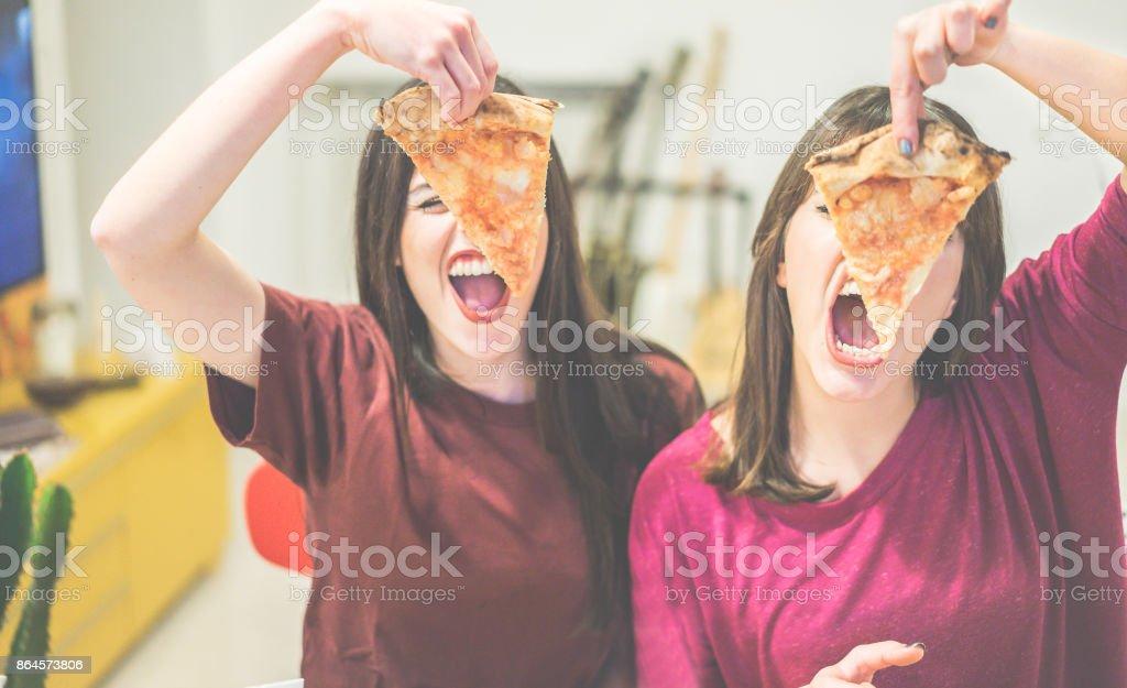 Zwei Freundinnen halten Pizzastücke vor den Gesichtern - junge Leute, die Spaß beim Abendessen - Rebel Konzept - Fokus auf linke Scheibe - warme filmische Filter – Foto