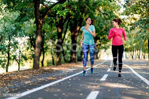 Two female friends jogging on path in sunny park