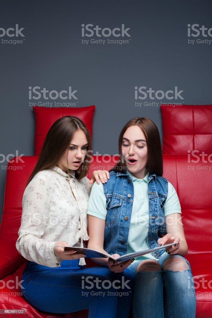 Dos amigas buscar revista de moda foto de stock libre de derechos