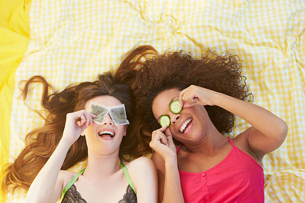 Two Female Friends Lying On Bed Using Beauty Treatments stock photo