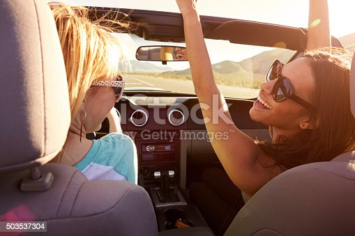 619068028 istock photo Two Female Friends On Road Trip Driving In Convertible Car 503537304