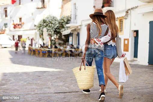 istock Two female friends on vacation shopping in Ibiza, back view 639747994