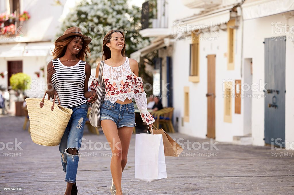 Two female friends on vacation shopping in Ibiza, front view - foto stock