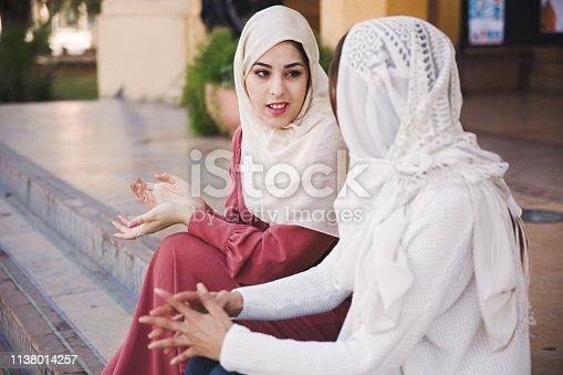 Two women of middle eastern descent walk through the city