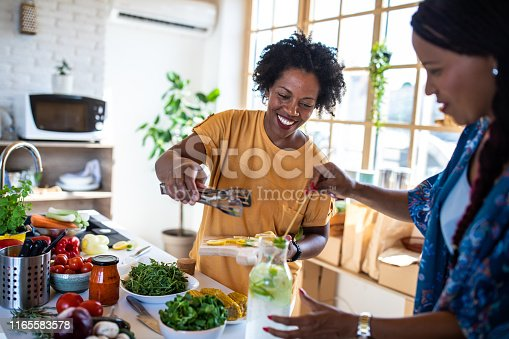 African woman and her friend preparing fresh lemon juice in the kitchen, cutting lemons