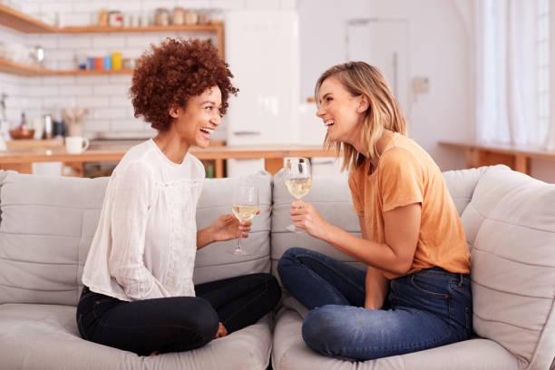 zwei weibliche freundinnen entspannen sich auf sofa zu hause mit glas des weins zusammen - freundin stock-fotos und bilder