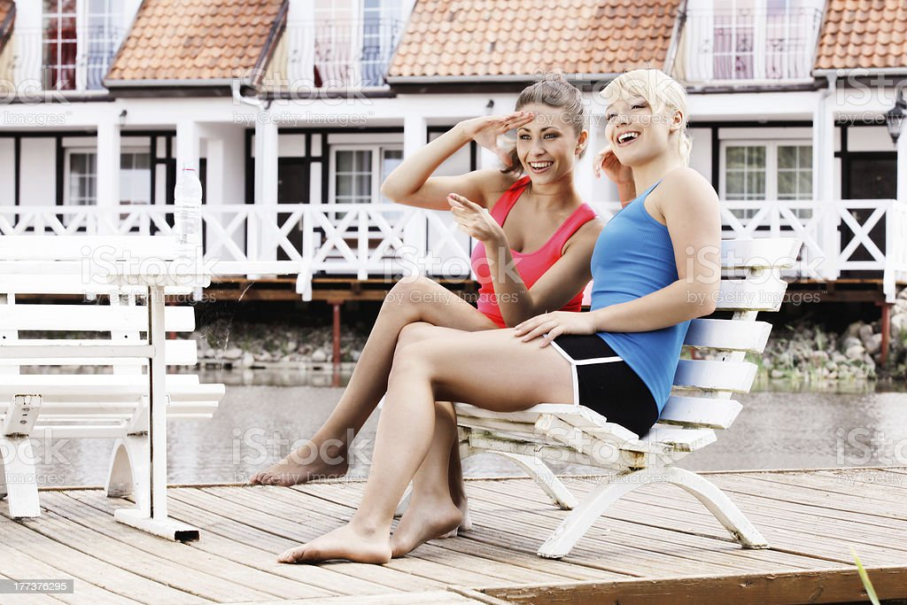 Two female friends resting on bench stock photo