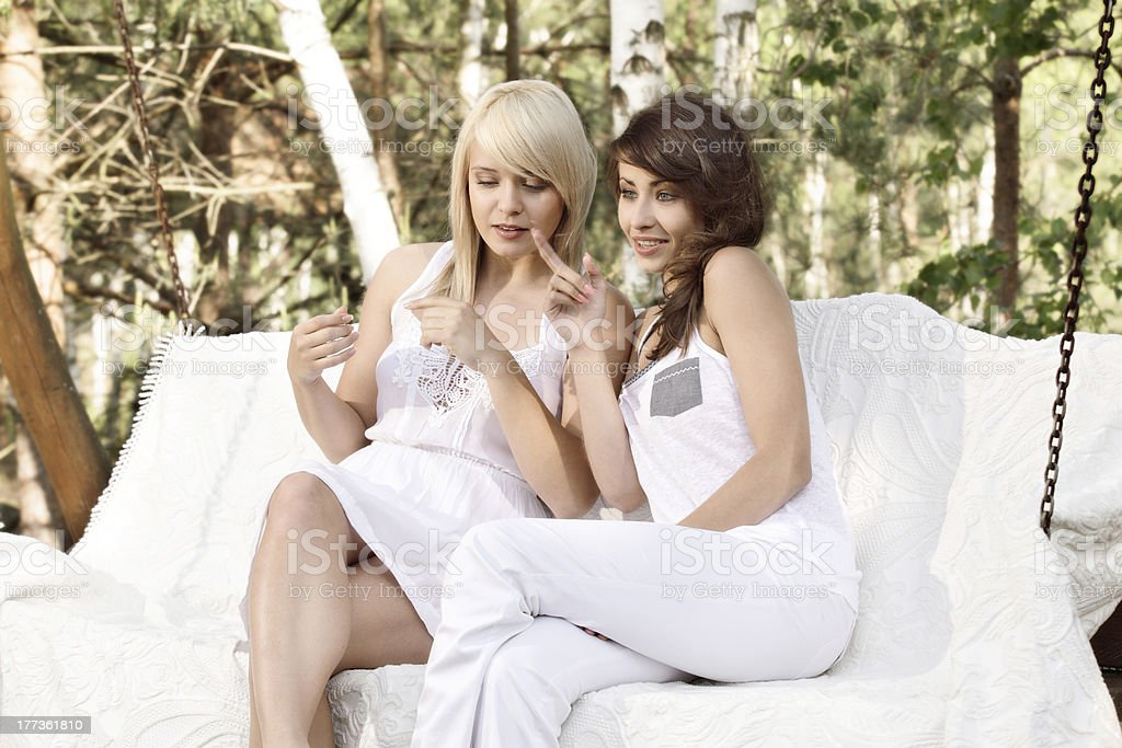 Two female friends resting on swing stock photo
