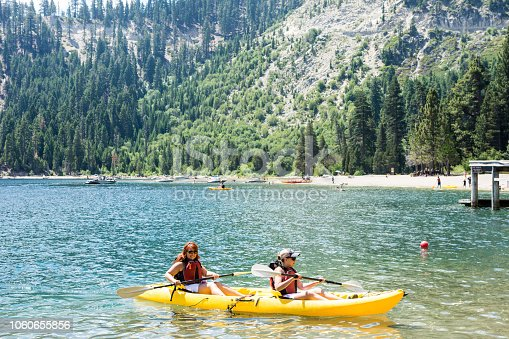 Two female friends row in a dual kayak on Lake Tahoe in Emerald Bay. Concept for teamwork, female friendship, working together