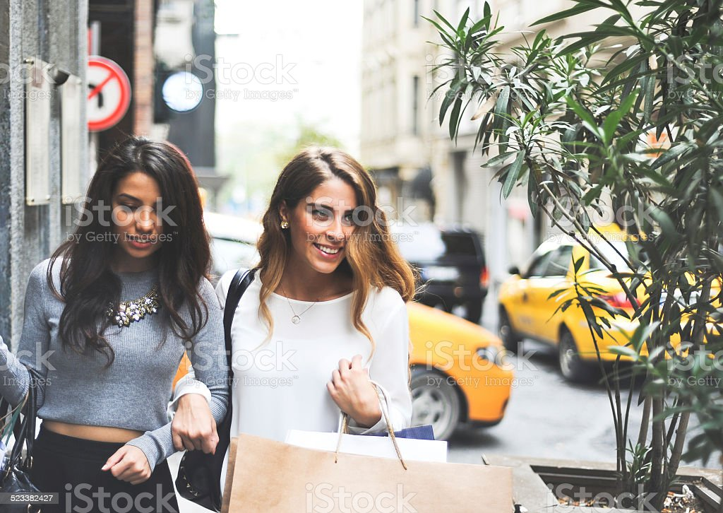 two female friends shopping and chatting on the street stock photo
