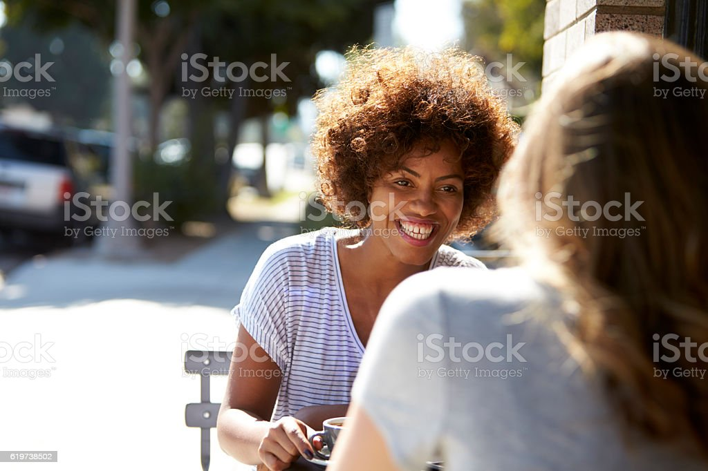 Two female friends sitting at a table outside a cafe stock photo