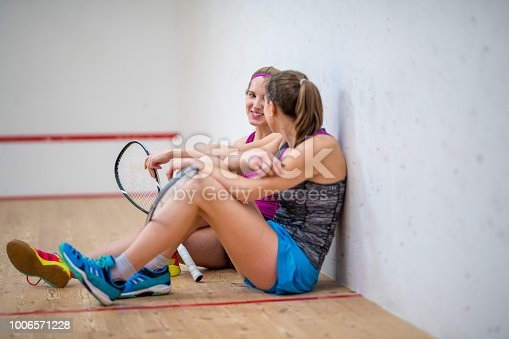 Two female friends sitting in squash court after their game and smiling while talking.