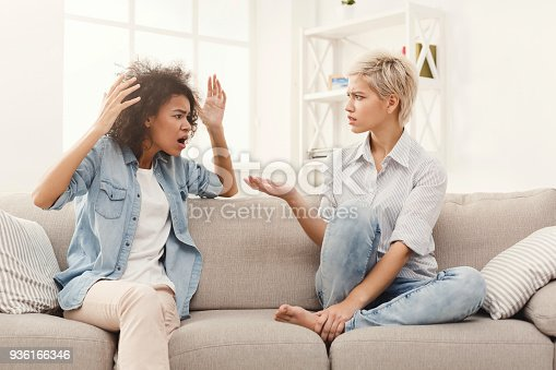 istock Two female friends sitting on sofa and arguing 936166346