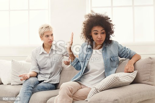 istock Two female friends sitting on sofa and arguing 936166508
