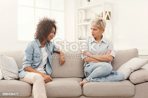 istock Two female friends sitting on sofa and arguing 936406472