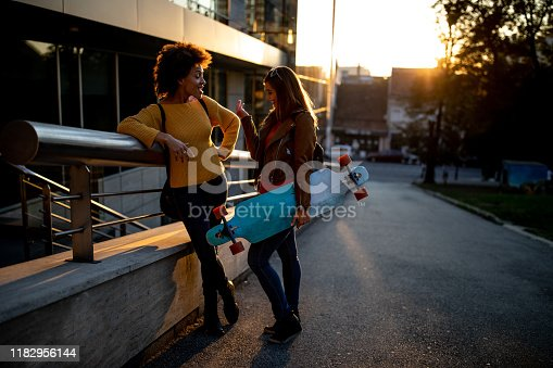 Two female friends standing outdoors and talking