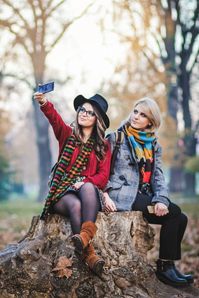 two female friends taking a selfie with smartphone - beautiful college girl pics stock photos and pictures