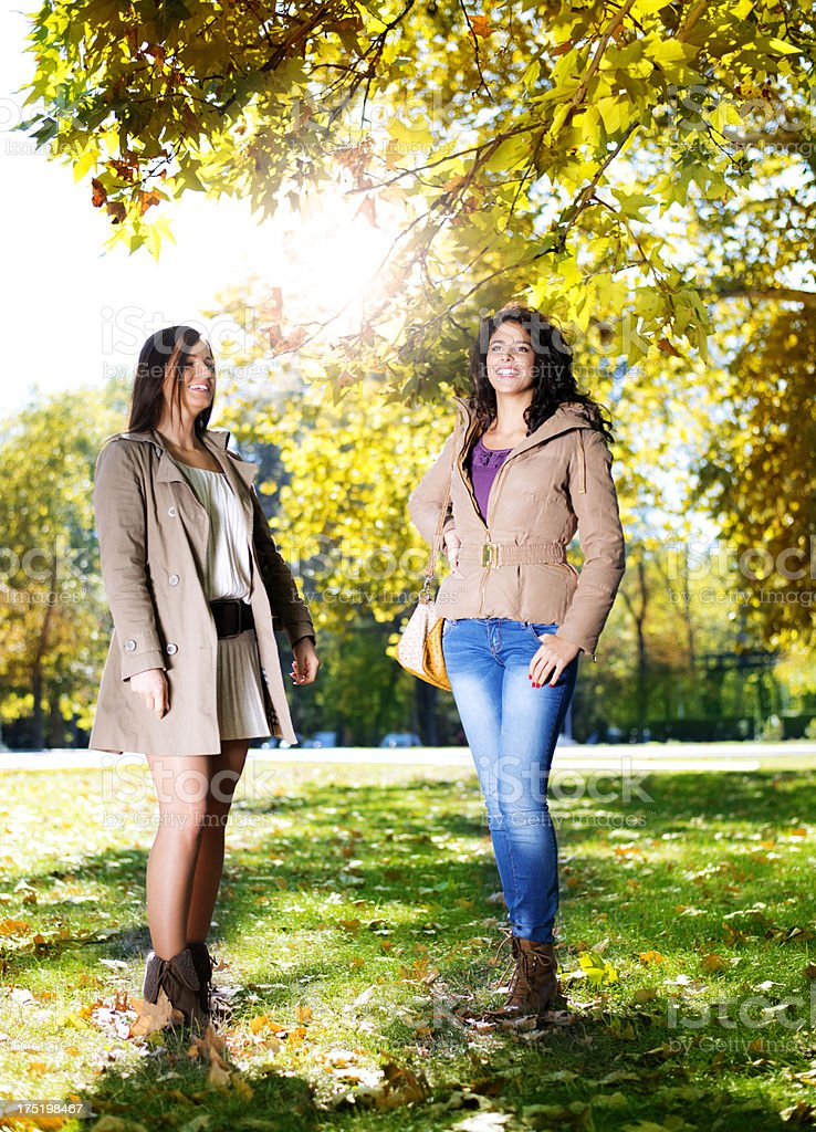 Two female friends taking a walk in the park royalty-free stock photo