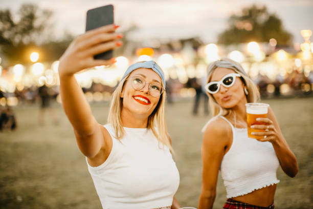 Two female friends taking selfie at music festival stock photo