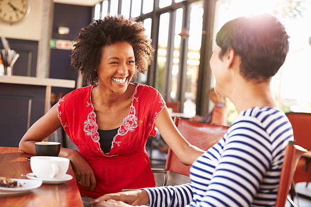 Two female friends talking at a coffee shop stock photo