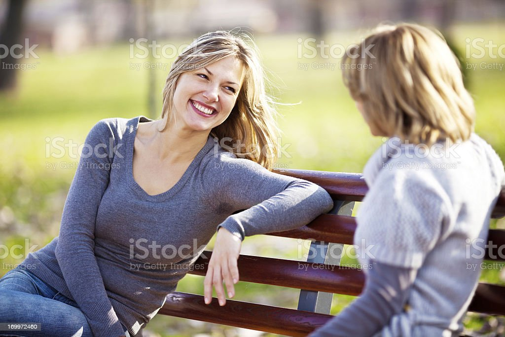 Two female friends talking in a park. royalty-free stock photo