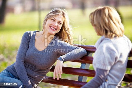 Two cheerful beautiful women sitting on the bench in the park and having a conversation.