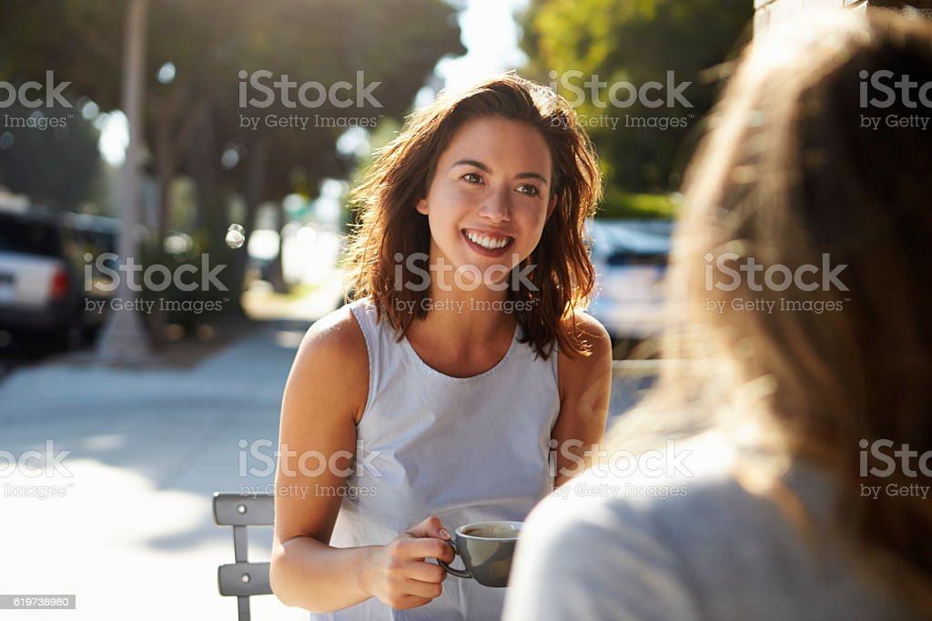 Two female friends talking over coffee outside a cafe stock photo