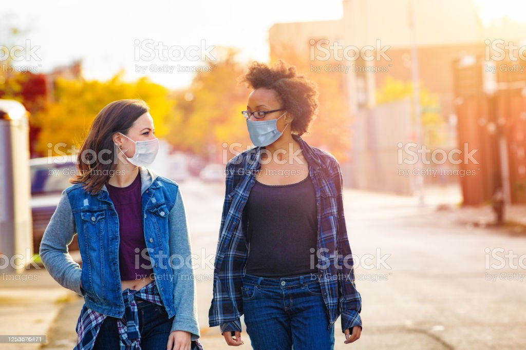 Two female friends walking down a Brooklyn alley wearing face masks Two female friends walking down a Brooklyn alley wearing face masks on a sunny Autumn day, having a quiet conversation. 20-29 Years Stock Photo