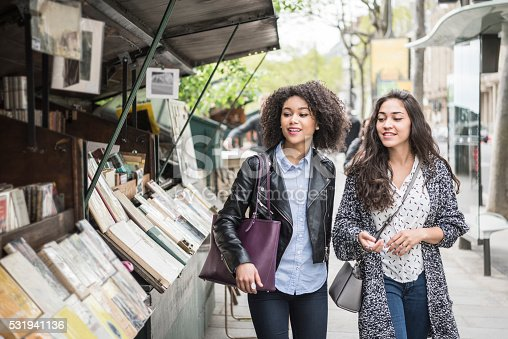 Two young women looking at second hand books in an outdoor book store. Two female friends out shopping in Paris, France