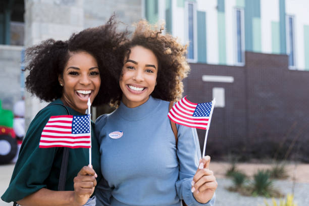 Two female friends wave flags and smile after voting stock photo