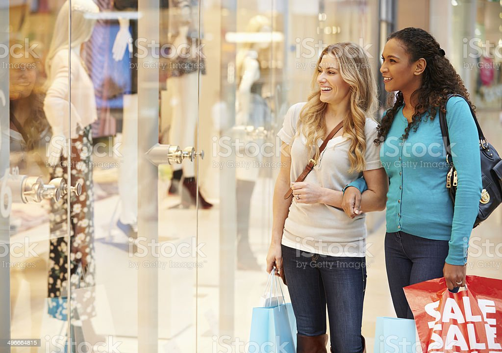 Two Female Friends Window Shopping With Bags stock photo