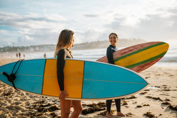 Two female friends with surfboards stock photo